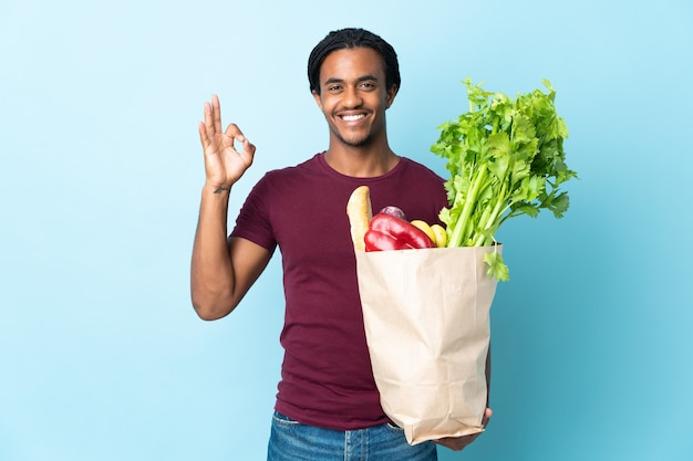 Homem afro-americano segurando uma sacola de compras de supermercado isolada em um fundo azul, mostrando o sinal de ok com os dedos
