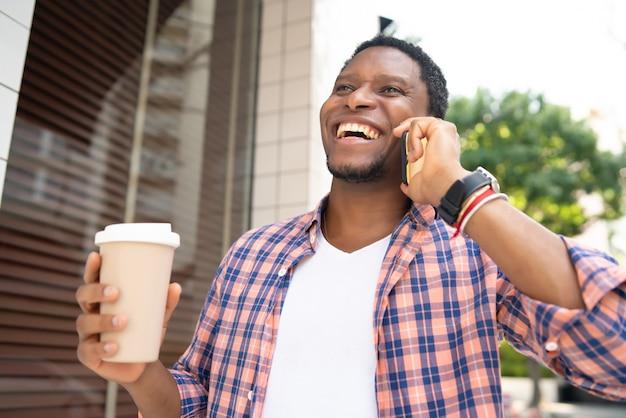 Homem afro-americano, segurando uma xícara de café e falando ao telefone enquanto caminhava na rua.