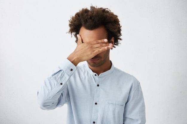 Homem afro-americano sem barbear irreconhecível com cabelo despenteado fazendo gesto com a palma da mão no rosto