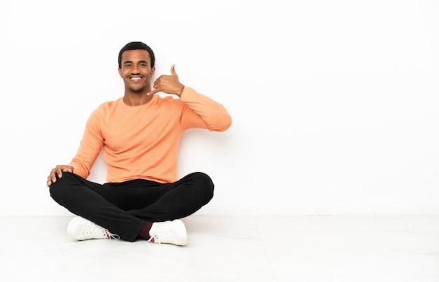 Homem afro-americano sentado no chão sobre o fundo isolado copyspace fazendo gesto de telefone. ligue-me de volta sinal