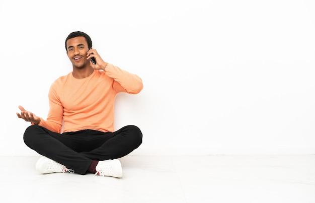 Homem afro-americano sentado no chão sobre um fundo isolado copyspace, conversando com alguém ao telefone celular