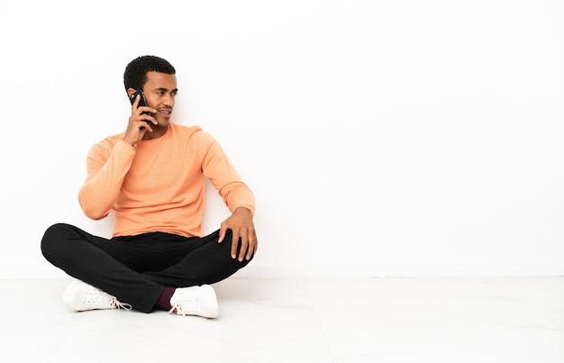 Homem afro-americano sentado no chão sobre um fundo isolado copyspace, conversando com alguém ao telefone celular Foto Premium