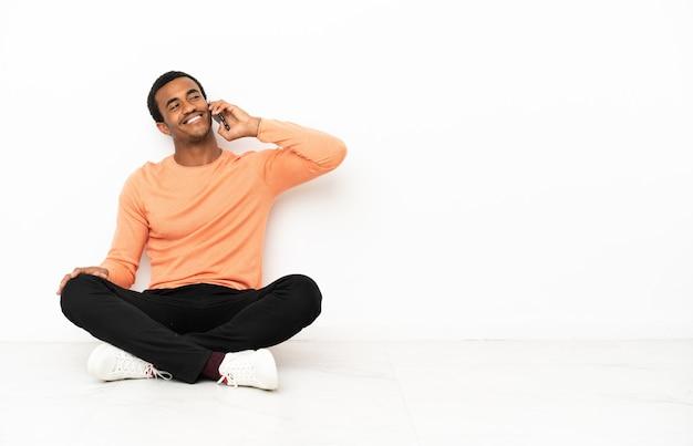 Homem afro-americano sentado no chão sobre um fundo isolado copyspace, conversando com o telefone celular Foto Premium
