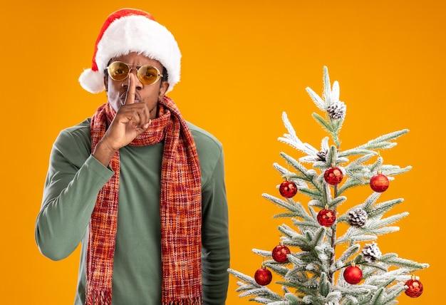 Homem afro-americano sério com chapéu de papai noel e lenço no pescoço fazendo gesto de silêncio com o dedo nos lábios ao lado de uma árvore de natal sobre fundo laranja