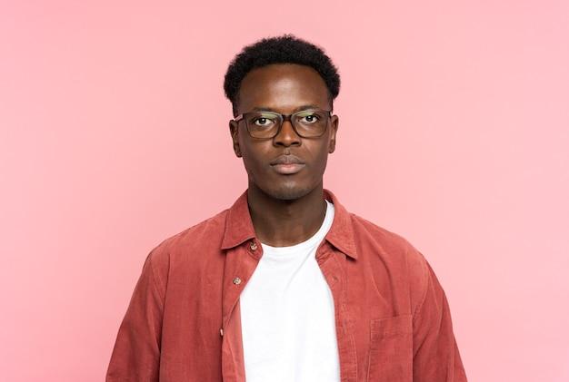 Homem afro-americano sério de óculos usa camisa vermelha, olhando para a câmera em pé, isolada no rosa