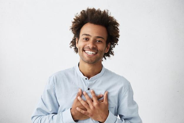 Homem afro-americano simpático e simpático, de camisa branca, sorriso encantador e expressão amigável