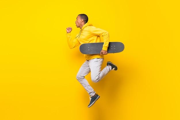 Homem afro-americano skatista sobre parede branca isolada
