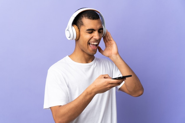 Homem afro-americano sobre música de parede roxa isolada com um celular e cantando