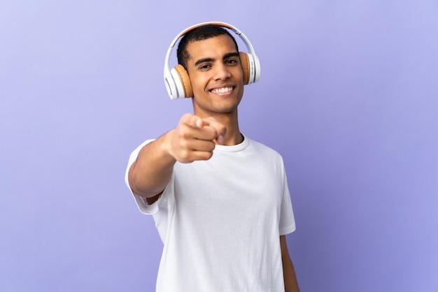 Homem afro-americano sobre parede roxa isolada, ouvir música e apontando para a frente