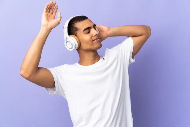 Homem afro-americano sobre parede roxa isolada, ouvir música e dançar