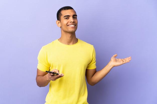Homem afro-americano sobre parede roxa isolada usando telefone celular segurando copyspace imaginário na palma da mão