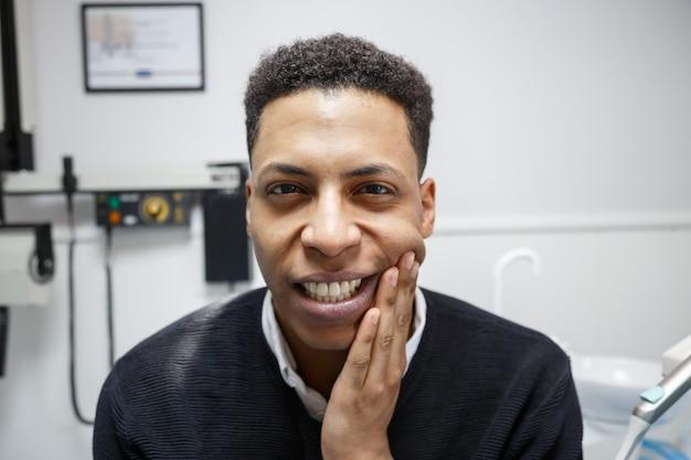Homem afro-americano sofrendo de dor de dente e reclamando durante visita ao dentista profissional.