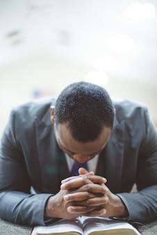 Homem afro-americano solitário orando com as mãos na bíblia e a cabeça baixa
