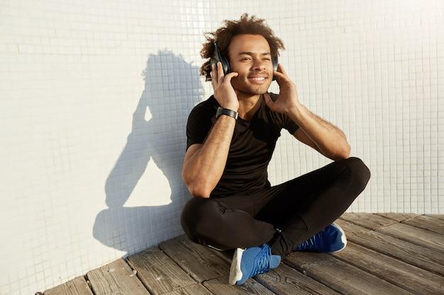 Homem afro-americano sorridente alegre com penteado espesso usando fones de ouvido grandes.