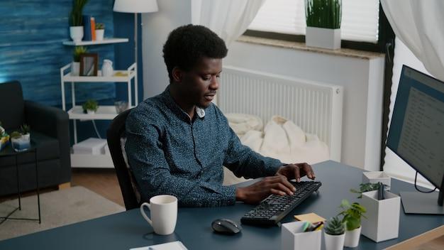 Homem afro-americano sorridente autêntico, trabalhando em casa, usuário de computador de trabalho remoto. foto em câmera lenta de freelancer usando comunicação on-line com internet na web em apartamento moderno