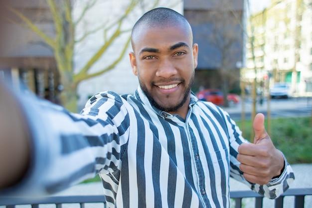 Homem afro-americano sorridente bonito aparecendo polegar
