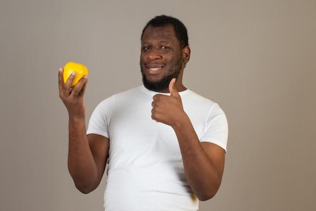 Homem afro-americano sorridente com um marmelo em uma das mãos e fazendo o sinal perfeito com a outra, em frente à parede cinza.
