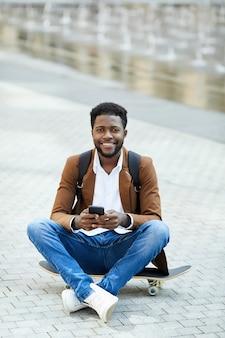Homem afro-americano sorridente texting na praça da cidade