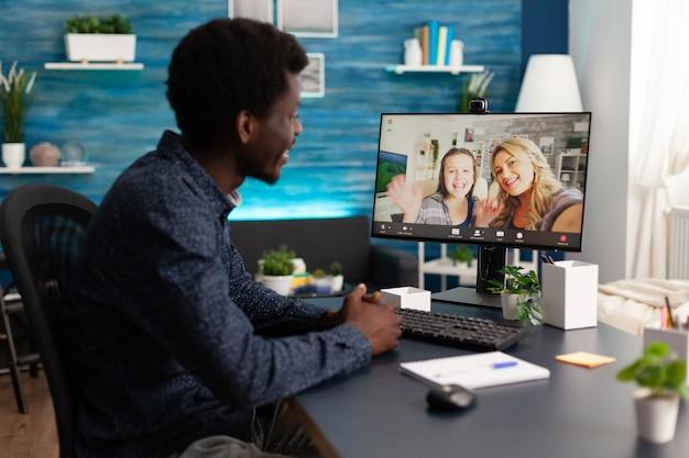 Homem afro-americano, tendo uma reunião de videochamada online discutindo ideias de marketing com amigos remotos durante o bloqueio de coronavírus. teletrabalho de videoconferência na tela do computador