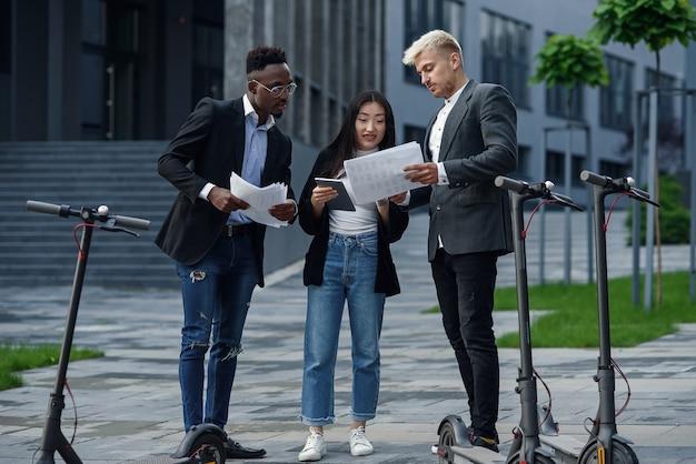 Homem afro-americano trabalhador, caucasiano, e uma menina asiática, em pé perto de um prédio comercial, analisando o projeto conjunto