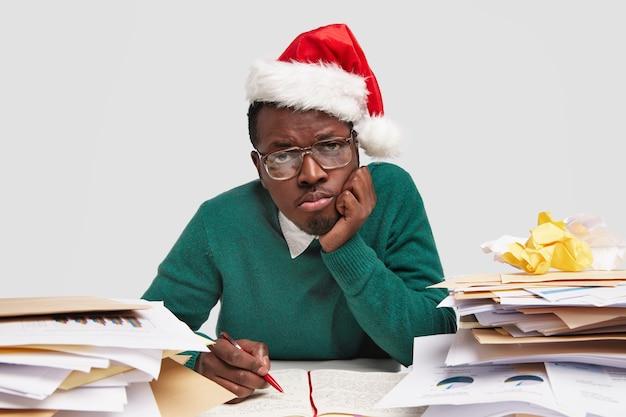 Homem afro-americano triste e sobrecarregado de trabalho mantém a mão na bochecha, usa chapéu de papai noel, óculos ópticos, escreve no diário