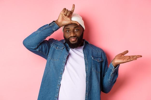 Homem afro-americano triste mostrando sinal de perdedor na testa e olhando para a câmera, em pé sobre um fundo rosa