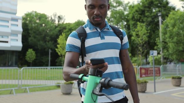 Homem afro-americano turístico pega scooter elétrica compartilhando aplicativo de telefone turístico de estacionamento. o homem desbloqueou a scooter elétrica com seu smartphone