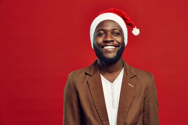 Homem afro-americano, usando chapéu de papai noel no vermelho