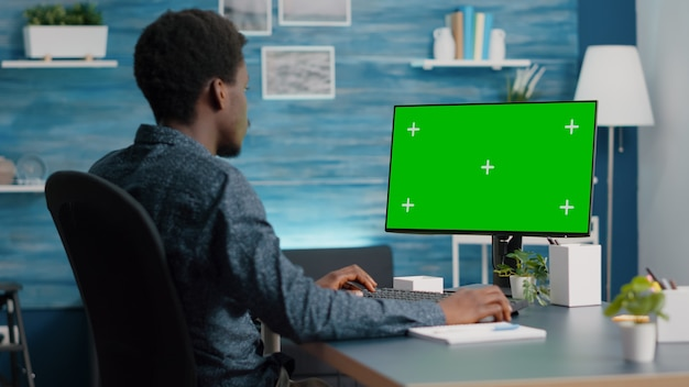 Homem afro-americano, usando e digitando no computador de maquete com tela verde. usuário de computador em monitor isolado de simulação de croma na sala de estar, casa iluminada