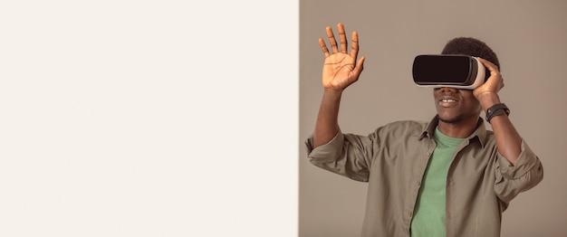 Homem afro-americano usando espaço de cópia de fone de ouvido de realidade virtual