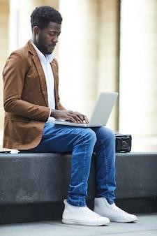 Homem afro-americano usando laptop na cidade