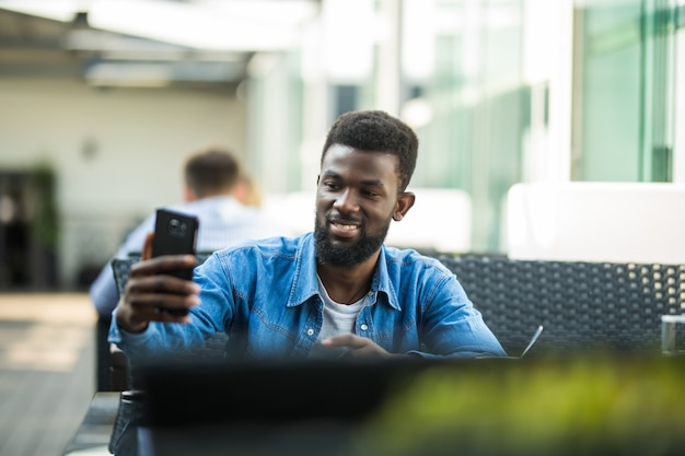 Homem afro-americano usando o bate-papo por vídeo por telefone, sentado à mesa em um café, copie o espaço