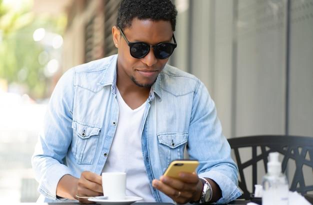 Homem afro-americano, usando seu telefone celular enquanto está sentado em uma cafeteria.