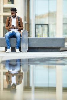 Homem afro-americano usando smartphone na cidade