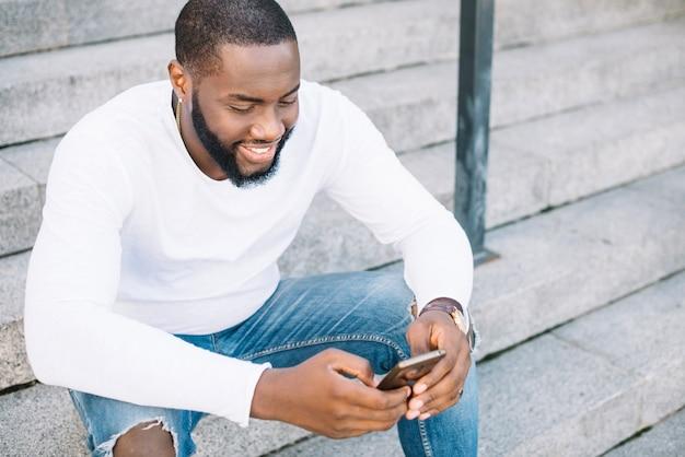 Homem afro-americano usando smartphone nas escadas