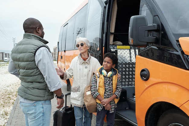 Homem afro-americano vestindo colete, colocando a avó e o filho no ônibus e ouvindo a promessa das avós