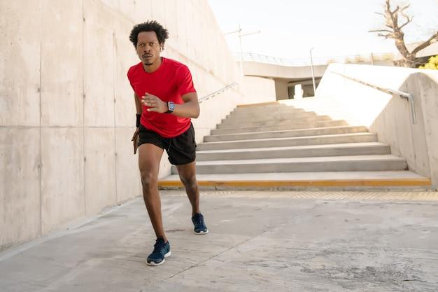 Homem afro-atlético correndo e fazendo exercício ao ar livre na rua. esporte e conceito de estilo de vida saudável.