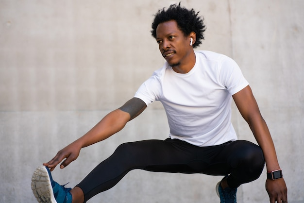 Homem afro-atlético, esticando as pernas e se aquecendo antes do exercício ao ar livre. esporte e conceito de estilo de vida saudável.