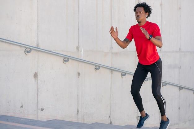 Homem afro-atlético fazendo exercício ao ar livre nas escadas. esporte e estilo de vida saudável.