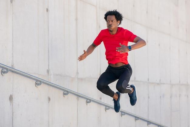 Homem afro-atlético fazendo exercícios ao ar livre em escadas