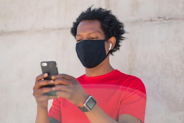 Homem afro-atlético usando máscara facial e usando seu telefone celular depois do treino ao ar livre. conceito de esportes e tecnologia. novo estilo de vida normal.
