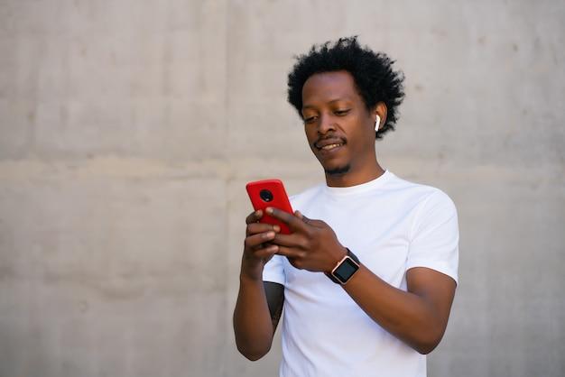 Homem afro-atlético usando seu telefone celular e relaxando depois do treino ao ar livre.