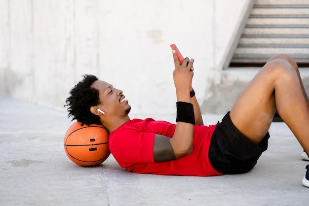Homem afro-atlético usando seu telefone celular e relaxando depois do treino ao ar livre