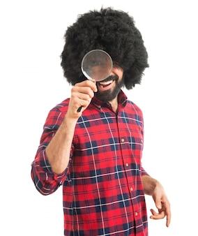 Homem afro com lupa
