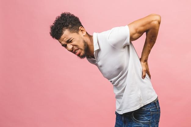 Homem afro com pé sobre fundo rosa isolado sofrimento de dor nas costas, tocando de volta com a mão, dor muscular.