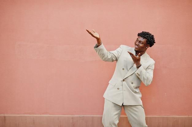 Homem afro elegante em terno bege da velha escola contra parede rosa. na moda jovem africano masculino em jaqueta casual no torso nu.