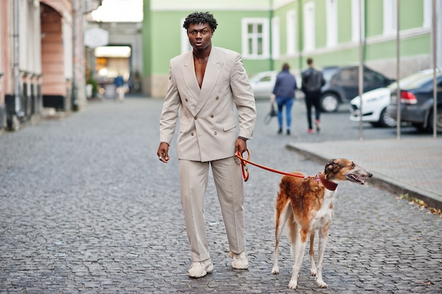 Homem afro elegante terno bege da velha escola com cachorro borzoi russo. na moda jovem africano masculino em jaqueta casual no torso nu.