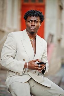 Homem afro elegante terno bege da velha escola com o celular na mão. na moda jovem africano masculino em jaqueta casual no torso nu.