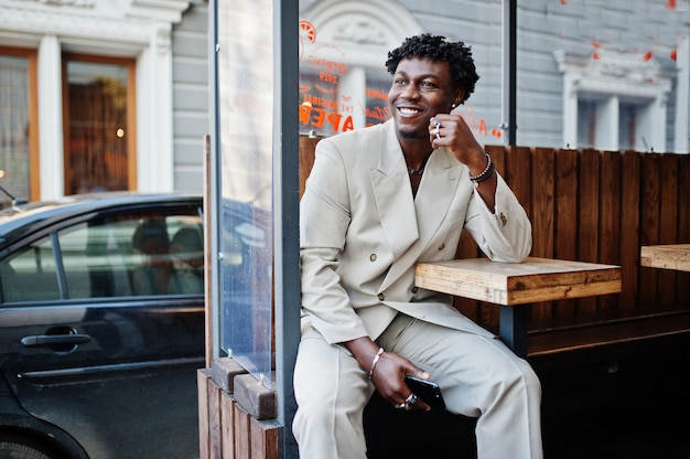 Homem afro elegante terno bege da velha escola sentar à mesa na rua. na moda jovem africano masculino em jaqueta casual no torso nu.