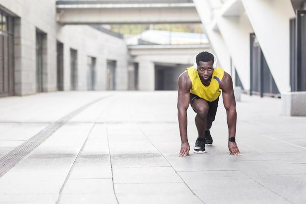 Homem afro em pose de início de corrida na rua da cidade. tiro ao ar livre, de manhã. primavera ou verão